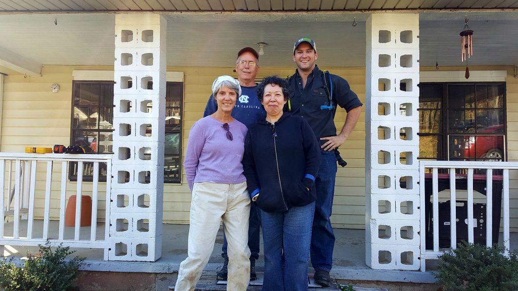 Executive Director Brad Rouse, Program Director Pearson King, Development Director Alice Wyndham, and homeowner Maria stand in front of Maria's house after a volunteer workday.